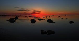 Tijdtijdspanne van rode zonsondergang boven een stille overzees