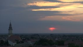 Tijdtijdspanne van zonsondergang boven een kleine Europese stad stock footage