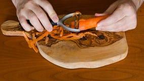 Tijdtijdspanne waarin drie wortelen worden gepeld stock video