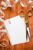 Tijeras, cinta de la medida y hoja de papel vacía Foto de archivo