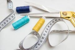 Tijeras de oro, hilos azules, azules y amarillos, cinta métrica que miente en un fondo blanco, un sistema para cortar y costura foto de archivo libre de regalías