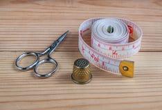 Tijeras, dedal, cinta métrica en el fondo del pueblo Fotografía de archivo libre de regalías
