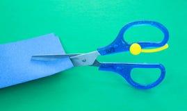 Tijeras del niño que cortan el papel Imagen de archivo
