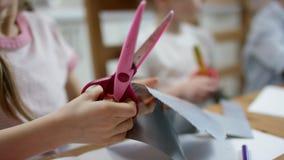 Tijeras del uso de la muchacha para cortar el papel coloreado cerca para arriba almacen de metraje de vídeo