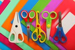 Tijeras en el fondo de los cuadernos coloreados de la escuela Imagen de archivo libre de regalías