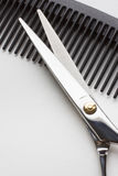 Tijeras para la operación del peluquero y un cepillo para el pelo en la parte posterior del blanco Imagenes de archivo
