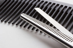 Tijeras para la operación del peluquero y un cepillo para el pelo en la parte posterior del blanco Imagen de archivo libre de regalías