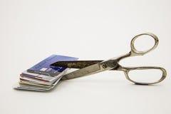 Tijeras que cortan las tarjetas de crédito plásticas que reducen deuda Imagen de archivo libre de regalías
