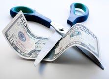 Tijeras que cortan a través de nota del dólar Foto de archivo libre de regalías