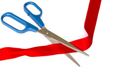 Tijeras que cortan una cinta roja imagen de archivo