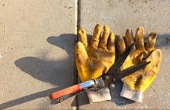 Tijeras que cultivan un huerto y guantes amarillos sucios Fotografía de archivo
