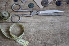 Tijeras y botones en un fondo de madera Imagenes de archivo