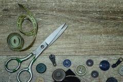Tijeras y botones en un fondo de madera imagen de archivo