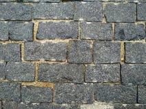 Tijolo de pedra Parede de tijolo da textura, telhas cinzentas brickly do close-up Fundo da textura da pedra da rua foto de stock