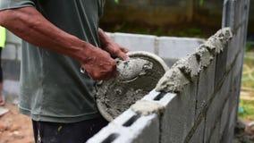 Tijolo do trabalhador a parede do cimento video estoque