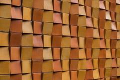 Tijolos alaranjados e amarelos decorativos que formam a parede exterior da cidade Imagens de Stock