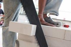Tijolos do corte do trabalhador com serra de fender imagem de stock