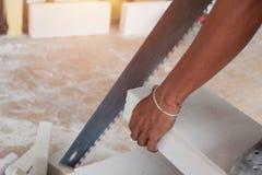 Tijolos do corte do trabalhador com serra de fender foto de stock