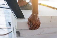 Tijolos do corte do trabalhador com serra de fender foto de stock royalty free