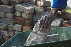 Tijolos, mãos e wheelbarrow Fotos de Stock