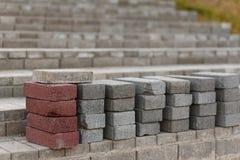 Tijolos vermelhos e tijolos cinzentos para pavimentar Colunas dos tijolos Colocando tijolos imagem de stock