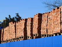 Tijolos vermelhos empilhados em cubos Tijolos do armazém Produtos das alvenaria do armazenamento Imagens de Stock
