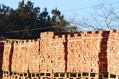 Tijolos vermelhos empilhados em cubos Tijolos do armazém Produtos das alvenaria do armazenamento Imagem de Stock