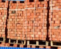 Tijolos vermelhos empilhados em cubos Tijolos do armazém Produtos das alvenaria do armazenamento Foto de Stock