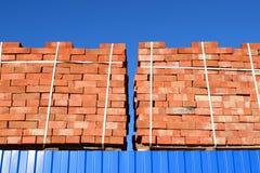 Tijolos vermelhos empilhados em cubos Tijolos do armazém Produtos das alvenaria do armazenamento Imagens de Stock Royalty Free