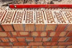 Tijolos vermelhos instalados com nível da construção Fotos de Stock Royalty Free