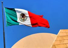 Mexican Flag Flying Over Cultural Center in Tijuana, Mexico. Tijuana, Mexico - October 30, 2017: Mexican flag flying over theater part of Cultural Center in royalty free stock photography
