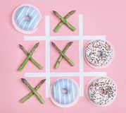 Tik tak toe game with donuts and asparagus. Health nutrition con. Cept image Royalty Free Stock Photos