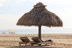 Tiki小屋和木头在海滩的躺椅 库存图片