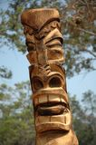 Tiki. Carving in front of tree royalty free stock photo