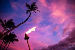Tiki fackla mot tropisk solnedgång Arkivfoton