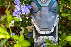 Tiki Garden. A tiki sculpture with flowers Stock Images