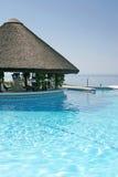 Tiki Hütte und Stab durch Swimmingpool des Luxushotels Lizenzfreies Stockfoto
