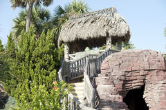 Tiki hut covering a goof golf course. Tiki Hut with wooden steps along the boardwalk at Pensacola Beach Stock Photos