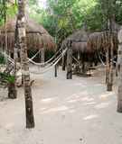 Tiki Huts in the sand. 3 thatched roof tiki huts in the sand with hammocks and chairs for relaxing Stock Image