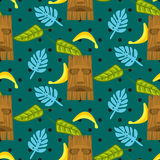 Tiki mask and palm leaves seamless vector pattern. Stock Image