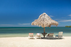 Tiki style umbrella shades four empty lounge chairs at water's edge Royalty Free Stock Images