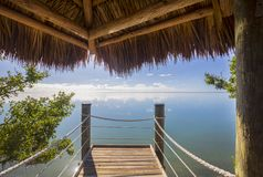 Tiki Thatch Dock On The Ocean. An ocean dock with marine rope under a tiki thatch roof stock photos
