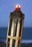 Tiki Torch. Lit with beach and sea as background Royalty Free Stock Image