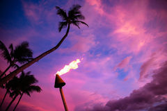 Tiki torch against tropical sunset Stock Photos
