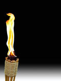 Tiki Torch on Black. Single burning tiki torch on white and black background Stock Photos