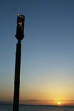 Tiki Torch Sunset. A tiki torch burning as the sun sets in paradise stock images