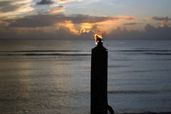 Tiki Torch at Sunset. Tiki Torch silhouetted against a backdrop of the Pacific Ocean with the sun setting in the background. The flame from the torch appears to Royalty Free Stock Photography