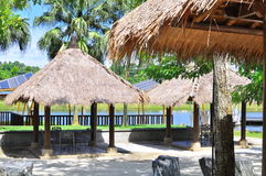 Tiki tropical hut. A tropical huts situated within a large garden which consists of palm trees , and lake Royalty Free Stock Photography