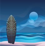 Tiki warrior mask wood surfboard ocean beach night Royalty Free Stock Photo