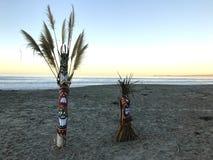 Tikis sur la plage au lever de soleil photographie stock